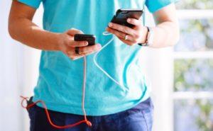 モバイルバッテリー片手にスマホゲームを嗜む男性